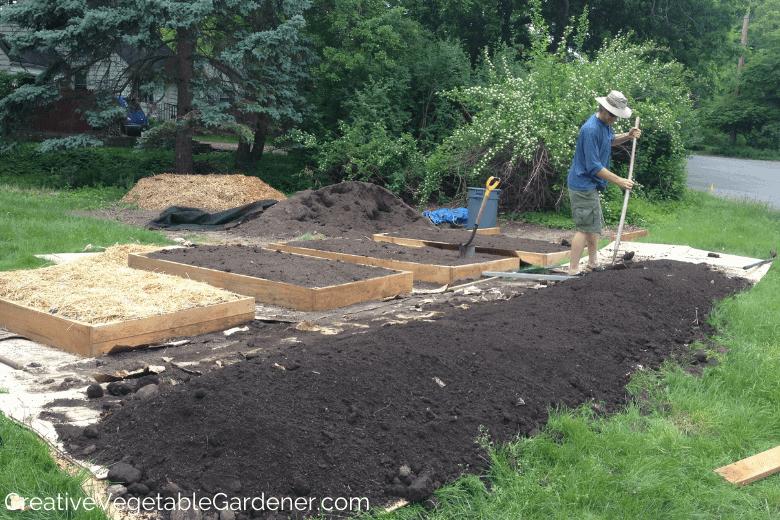 man raking soil in flower garden bed