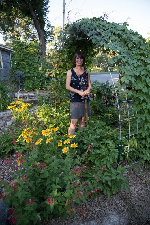 woman in garden under trellis