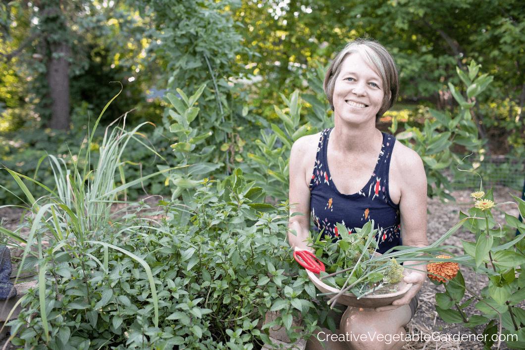 woman harvesting herbs from spiral garden