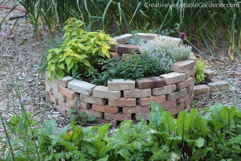 herb spiral in garden with resources for planning garden