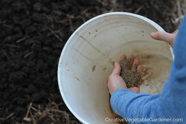 gardener adding organic garden fertilizer