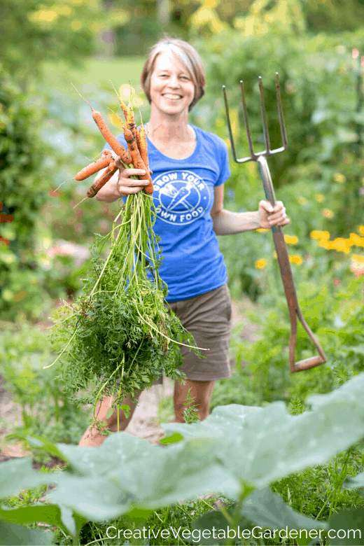 woman holding carrots to grow in a garden